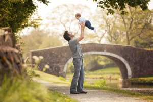 Blackburn photographer - Pendle Lancashire - Father throwing his baby son into the air beside a canal