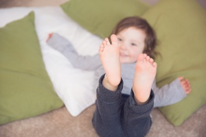 Pendle Lancashire - Toddler lying on cushions kicking her feet up