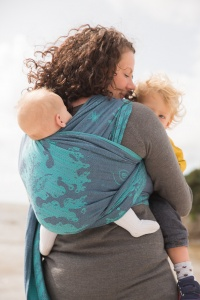 Carnforth Lancashire - Picture of a mother with her back to the camera holding her toddler in arms with one of her twin babies on her back in a baby wrap