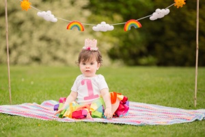 Clitheroe Ribble Valley - Baby sitting on a blanket with rainbow and cloud bunting above, wearing a rainbow tutu, vest with 1 on it, and a crown