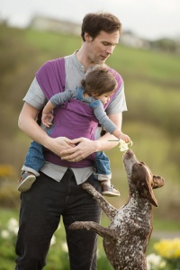 Jackhouse Nature Reserve Oswaldtwistle - Father carrying his son in an Izmi carrier, their dog is jumping up to grab the daffodil from the boy's hand