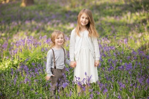 Blackburn outdoor photographer - - Photo of a girl and boy smiling while standing among bluebells