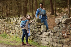 Entwistle Reservoir - Portrait of a mum and dad carrying their two children in Baie Sling wrap while leaning on a wall