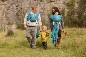 Blackburn family photographer - Mum and dad carrying their twins and holding their little boy's hands walking