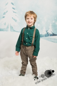 Christmas mini photo sessions for children - A boy in a green shirt standing in front of a wintery scene