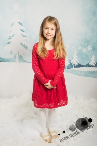 Christmas Mini Photo Session Darwen - A girl in a red dress standing in front of a wintery scene