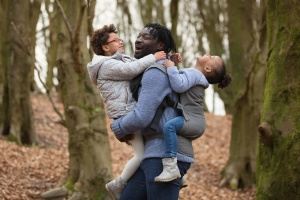 Roddlesworth Woods Tockholes - A father is older his older daughter in arms and carries his younger daughter on his back in an Izmi carrier, all are laughing