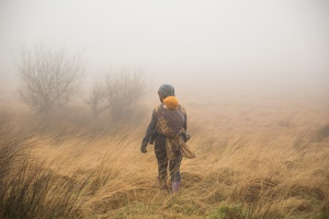 Belmont Lancashire - A woman carrying her baby on her back in a woven wrap walks towars the fog