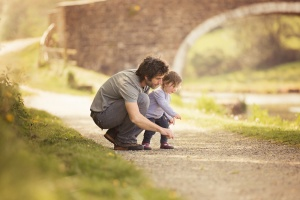 Pendle Lancashire - Beside a canal a father crouches next to his toddler daughter looking to where she is pointing