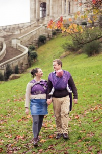 Williamson Park Lancaster - A couple walk away from the Aston Memorial carrying their twins in woven wraps