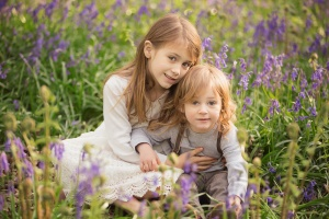 Spring Wood Whalley - A girl and boy sit cuddled together among bluebells