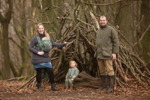 Roddlesworth Tockholes - A family of mum carrying baby in a woven wrap, dad, and toddler in front of a den in the woods