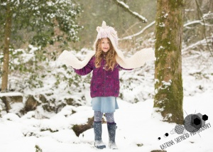 Bold Venture Park, Darwen - A girl stands on a log in the woods while snow falls around her