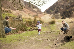 White Coppice, Chorley - Photo of a child running from her mum to her dad who are crouched down