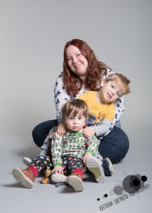 Happy Daze, Darwen - Portrait of mum and two boys sitting in front of one another towards the camera